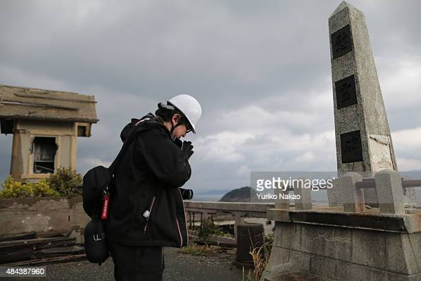 Director Shinji Higuchi folds his hands together in front of a memorial monument during a location hunting for his film 'Attack on Titan' on Hashima...
