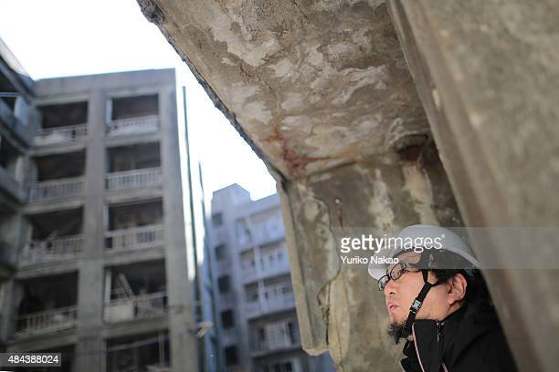 Director Shinji Higuchi looks at abandoned apartment building during a location hunting for his film 'Attack on Titan' on Hashima Island commonly...