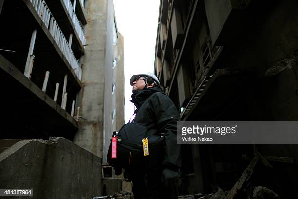 Director Shinji Higuchi looks up during a location hunting for his film 'Attack on Titan' on Hashima Island commonly known as Gunkanjima which means...
