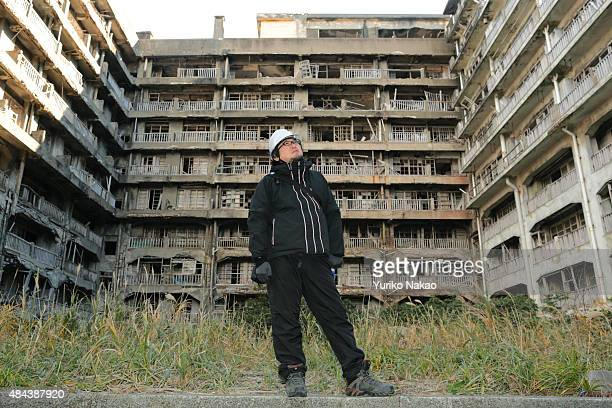 Director Shinji Higuchi poses in front of an abandoned apartment building during a location hunting for his film 'Attack on Titan' on Hashima Island...