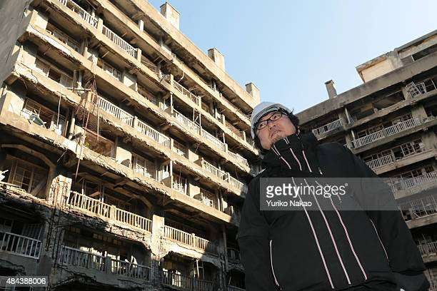 Director Shinji Higuchi poses in front of an apartment building during a location hunting for his film 'Attack on Titan' on Hashima Island commonly...