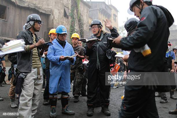 Director Shinji Higuchi talks with his filming crew on the set during the filming of 'Attack on Titan' on June 9 2014 in Takahagi Japan
