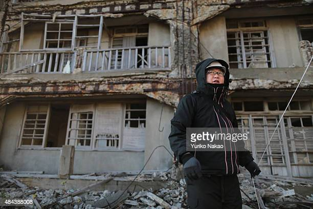 Director Shinji Higuchi walks in front of an abandoned building during a location hunting for his film 'Attack on Titan' on Hashima Island commonly...