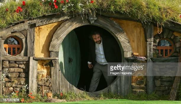 Director Sir Peter Jackson emerges from from a Hobbit house before delivering a speech at the 'The Hobbit An Unexpected Journey' World Premiere at...