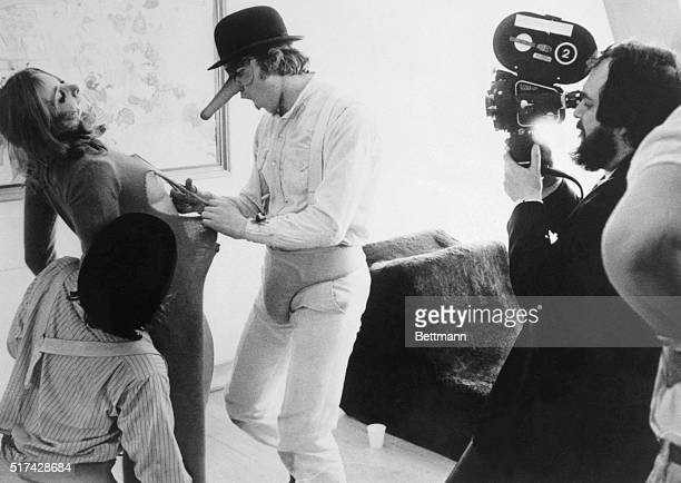 Director Stanley Kubrick filming closeup of little Alex in his phallic mask cutting the clothes off a woman he is about to rape in the picture A...