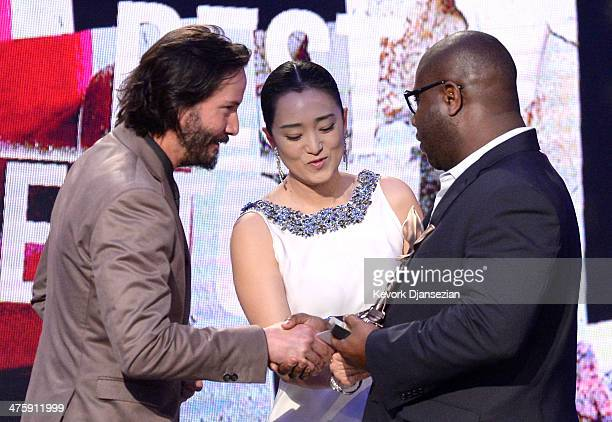 Director Steve McQueen accepts the Best Director award for '12 Years a Slave' from actors Keanu Reeves and Gong Li onstage during the 2014 Film...