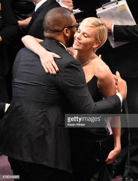 Director Steve McQueen and actress Charlize Theron speak in the audience during the Oscars at the Dolby Theatre on March 2 2014 in Hollywood...