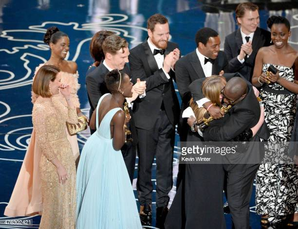 Director Steve McQueen embraces producer Bianca Stigter as they accept the Best Picture award for '12 Years a Slave' with actors Sarah Paulson Kelsey...