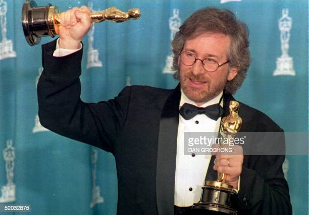 US director Steven Spielberg poses with his two Oscars 21 March 1994 in Los Angeles CA during the 66th Annual Academy Awards ceremony after winning...