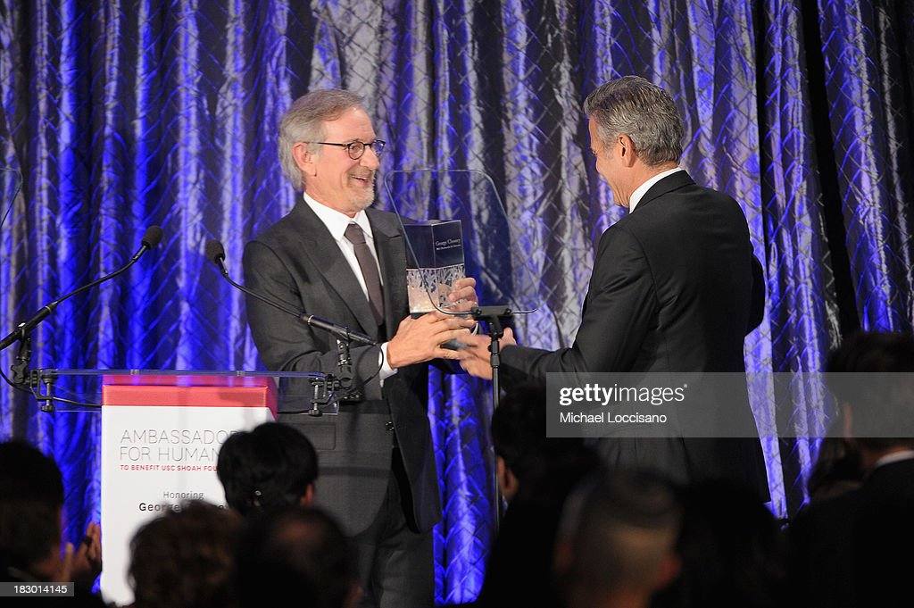 Director Steven Spielberg presents honoree George Clooney with the USC Shoah Foundation's Ambassador for Humanity Award at the USC Shoah Foundation Institute 2013 Ambassadors for Humanity gala at the American Museum of Natural History on October 3, 2013 in New York, New York.