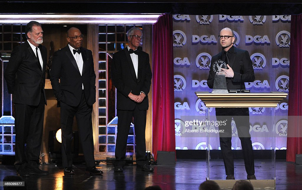 Director Taylor Hackford, DGA President Paris Barclay, director Michael Apted stand onstage as director Steven Soderbergh accepts the Robert B. Aldrich Service Award onstage at the 66th Annual Directors Guild Of America Awards held at the Hyatt Regency Century Plaza on January 25, 2014 in Century City, California.