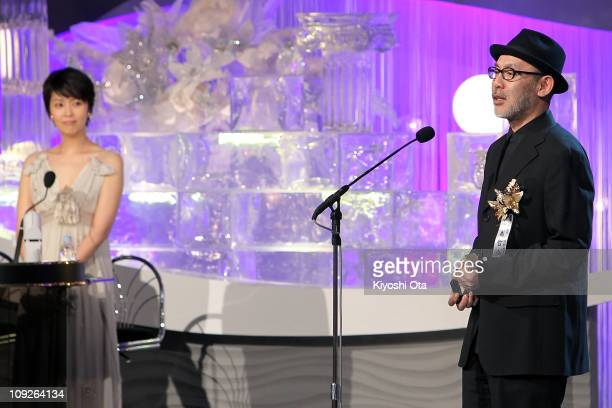 Director Tetsuya Nakashima speaks onstage as he accepts the award for Best Director for 'Kokuhaku ' while cast member Takako Matsu looks on during...