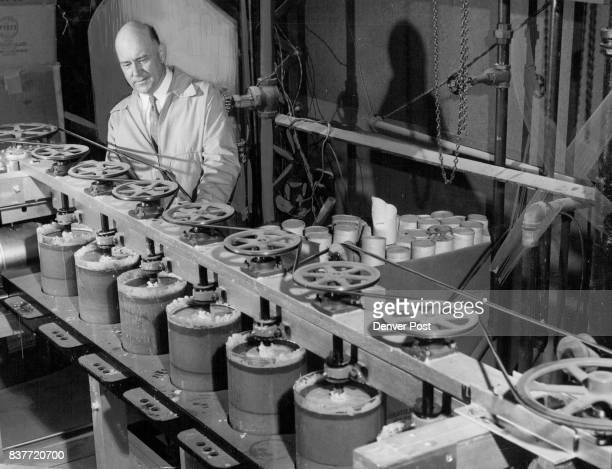Director Vernon L Mattson of the School of Mines research foundation checks on abrasion test machine to see which metal is best fitted for use in...