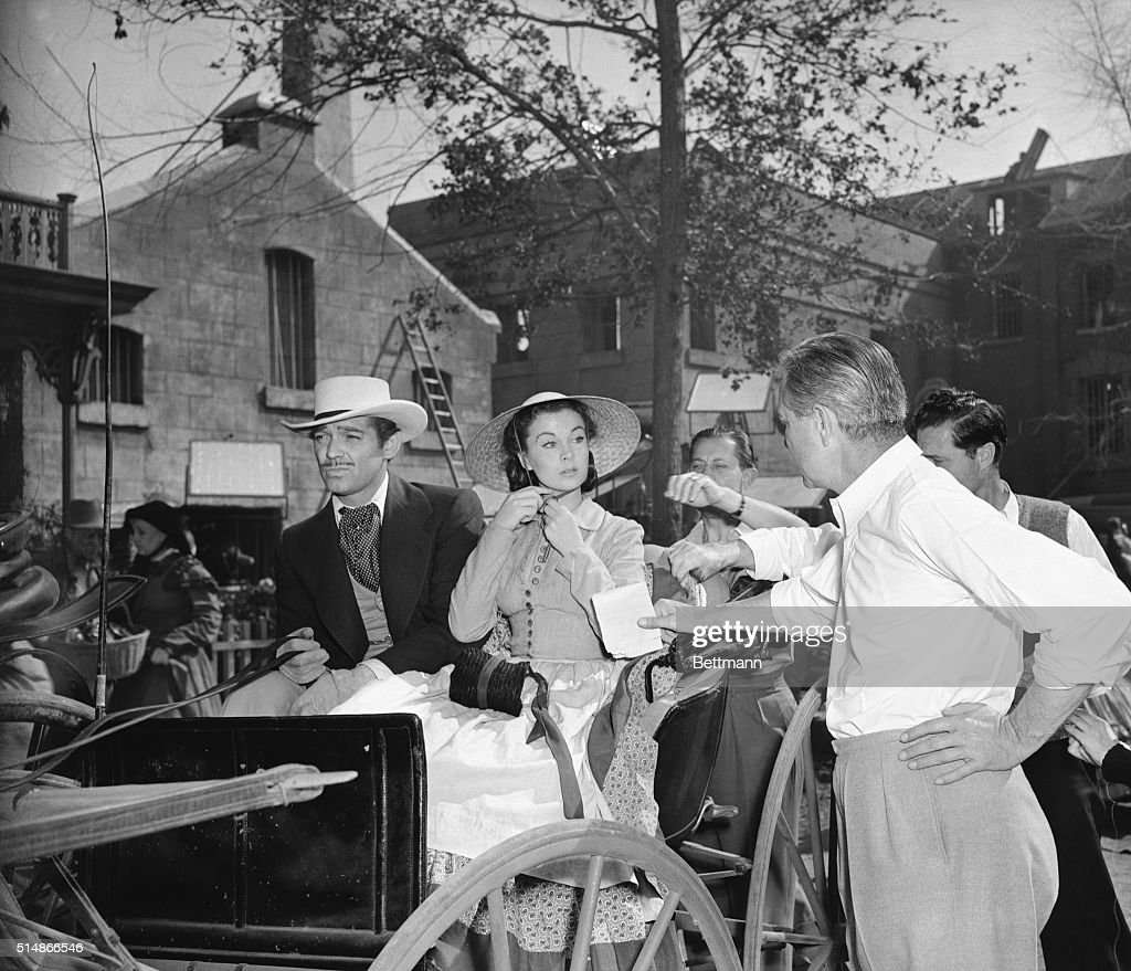 Director Victor Fleming talks to actress Vivien Leigh during the filming of Gone With the Wind Actor Clark Gable is seated beside her