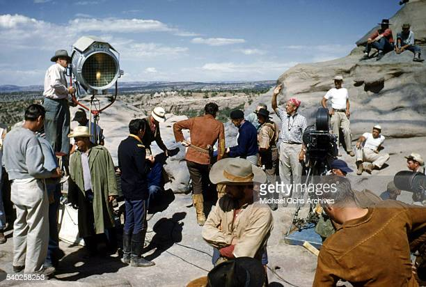 Director William Keighley over sees the script with actor Errol Flynn as the film crew films the movie 'Rocky Mountain' on location in Gallop New...