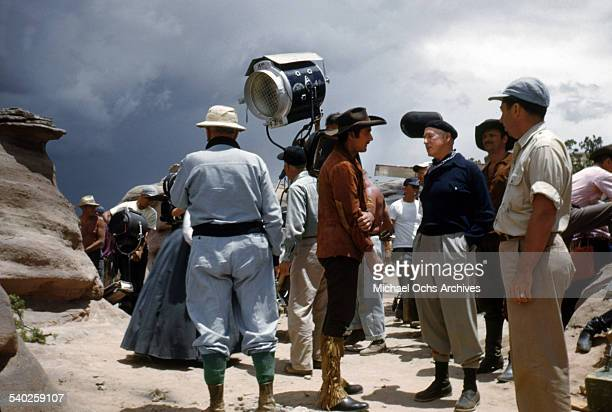 Director William Keighley talks with actor Errol Flynn as the film crew films the movie 'Rocky Mountain' on location in Gallop New Mexico Starring...