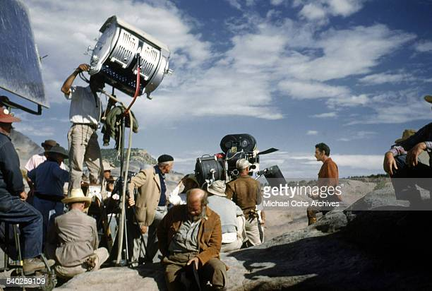 Director William Keighley watches actor Errol Flynn on set as the film crew films the movie 'Rocky Mountain' on location in Gallop New Mexico...
