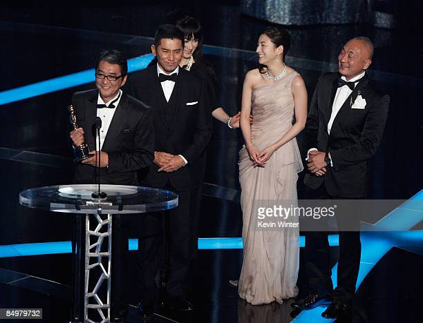 Director Yojiro Takita actor Masahiro Motoki actress Ryoko Hirosue and executive producer Yasuhiro Mase accepts the award for Best Foreign Language...