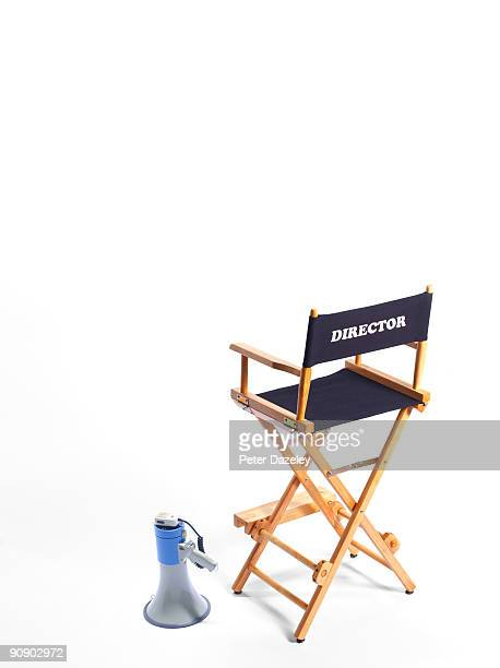 Directors chair and megaphone on white background.