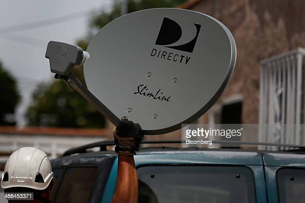 A DirecTV technician carries a new satellite TV dish while performing a new installation for a tenant at a apartment building in Lynwood California...
