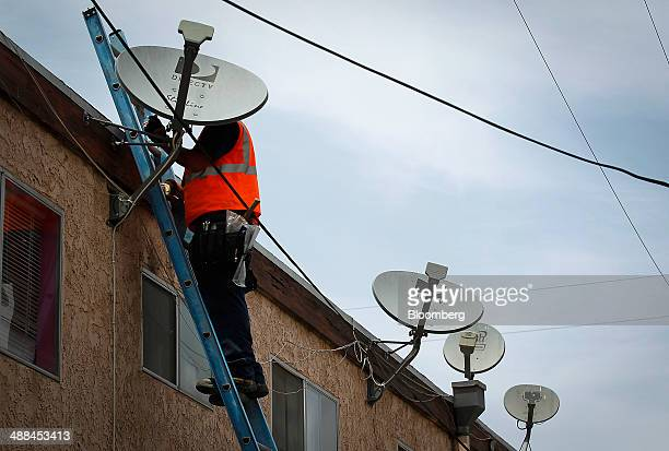 A DirecTV technician removes a satellite TV dish while performing a new installation for a tenant at a apartment building in Lynwood California US on...