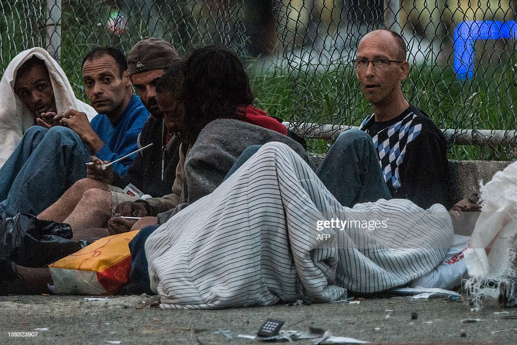 Dirk de Jong (R), 50-year-old Dutch tourist, stays on a sidewalk among drug addicts at 'Crackolandia', a place where drug users gather to smoke crack, in downtown Sao Paulo Brazil on January 11, 2013. About 3 weeks ago, Jong got all his belongings robbed and he settled at Crackolandia to get free food and clothes from a church. At first, he started selling stolen softdrink and after making a small amount of money started to sell single cigarettes or crack cocaine to survive. AFP PHOTO/Yasuyoshi CHIBA