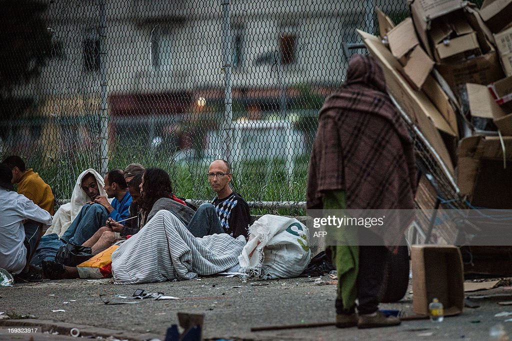 Dirk de Jong (2nd R), 50-year-old Dutch tourist, stays on a sidewalk among drug addicts at 'Crackolandia', a place where drug users gather to smoke crack, in downtown Sao Paulo Brazil on January 11, 2013. About 3 weeks ago, Jong got all his belongings robbed and he settled at Crackolandia to get free food and clothes from a church. At first, he started selling stolen softdrink and after making a small amount of money started to sell single cigarettes or crack cocaine to survive. AFP PHOTO/Yasuyoshi CHIBA