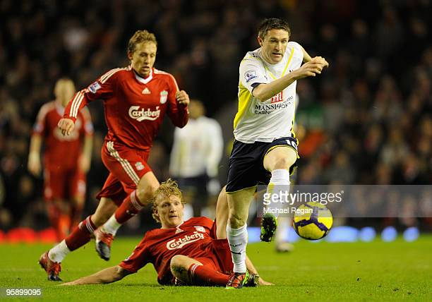Dirk Kuyt of Liverpool tackles Robbie Keane of Tottenham Hotspur during the Barclays Premier League match between Liverpool and Tottenham Hotspur at...