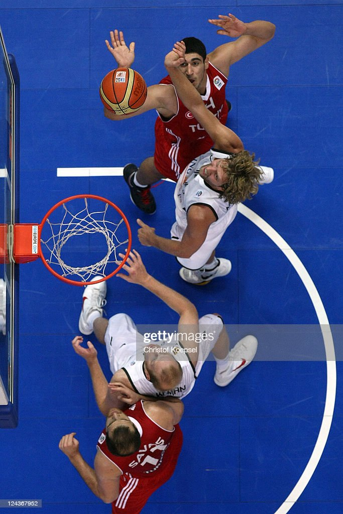 Dirk Nowitzki of Germany scores against Cenk Akyol of Turkey and Oguz Savaz of Turkey during the EuroBasket 2011 second round group E match between Germany and Turkey at Siemens Arena on September 9, 2011 in Vilnius, Lithuania.