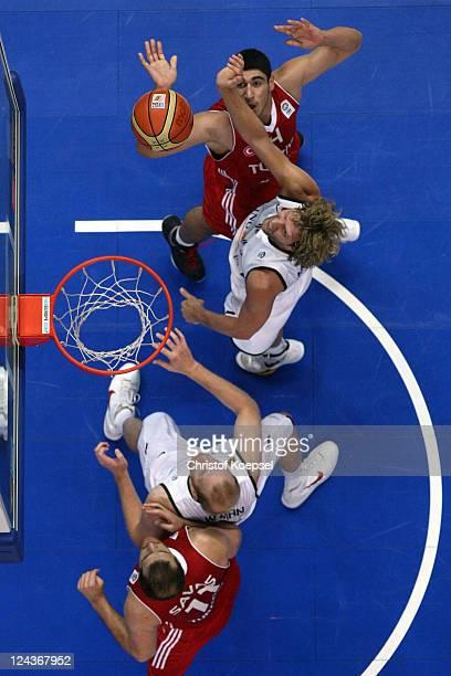 Dirk Nowitzki of Germany scores against Cenk Akyol of Turkey and Oguz Savaz of Turkey during the EuroBasket 2011 second round group E match between...