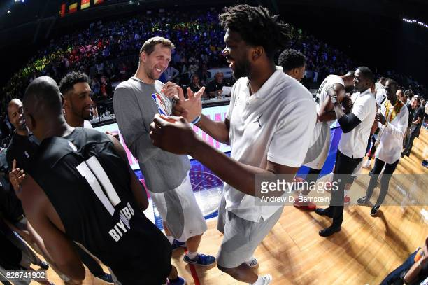 Dirk Nowitzki of Team World shakes hands with Joel Embiid of Team Africa in the 2017 Africa Game as part of the Basketball Without Borders Africa at...