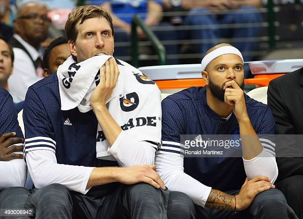 Dirk Nowitzki of the Dallas Mavericks and Deron Williams sit on the bench during a preseason game against the Atlanta Hawks at American Airlines...