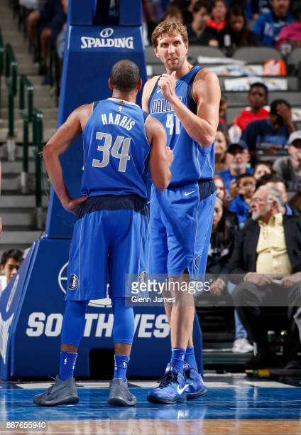 Dirk Nowitzki of the Dallas Mavericks and Devin Harris of the Dallas Mavericks discuss a play during the game against the Philadelphia 76ers on...