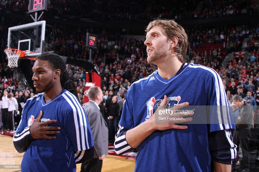 Dirk Nowitzki #41 of the Dallas Mavericks and Jae Crowder #9 of the Dallas Mavericks listen to the National Anthem while wearing Fit Week T-shirts during the game between the Dallas Mavericks and the Portland Trail Blazers on January 29, 2013 at the Rose Garden Arena in Portland, Oregon.