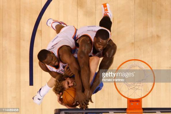 Dirk Nowitzki of the Dallas Mavericks attempts to go up for a shot against Serge Ibaka and Kendrick Perkins of the Oklahoma City Thunder in the...