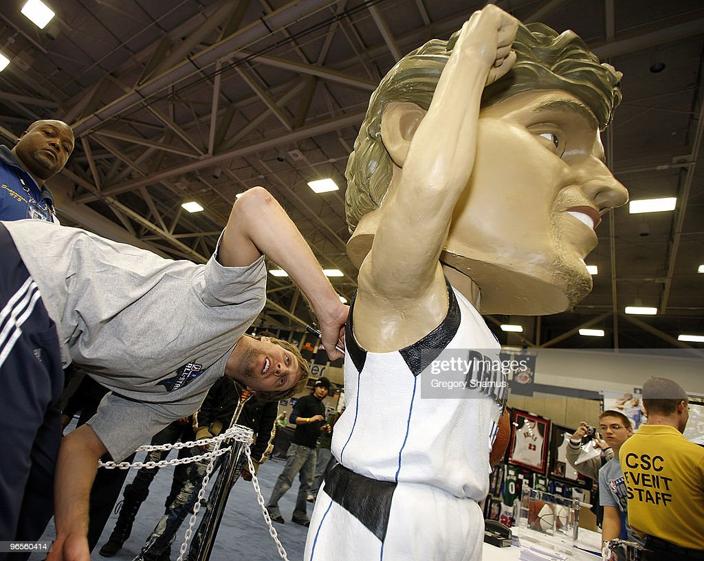 Dirk Nowitzki of the Dallas Mavericks autographs a life size bobblehead during a appearance at Jam Session presented by Adidas during NBA All Star...