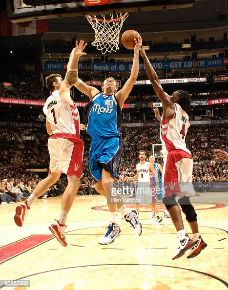 Dirk Nowitzki of the Dallas Mavericks drives the lane and splits defenders Andrea Bargnani and Chris Bosh of the Toronto Raptors during a game on...