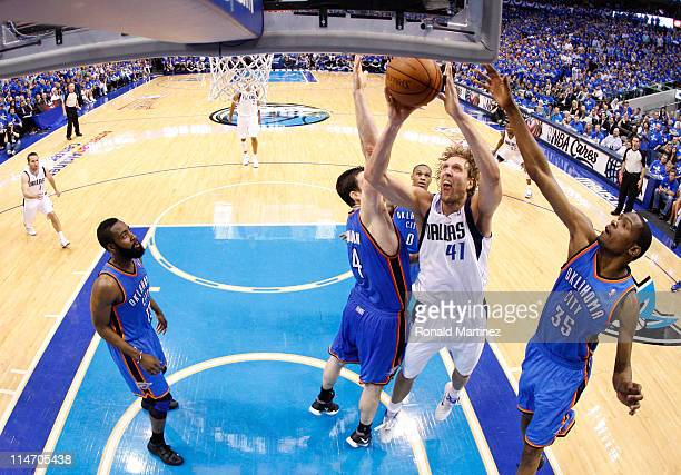 Dirk Nowitzki of the Dallas Mavericks goes up for a shot between Nick Collison and Kevin Durant of the Oklahoma City Thunder in the second half in...