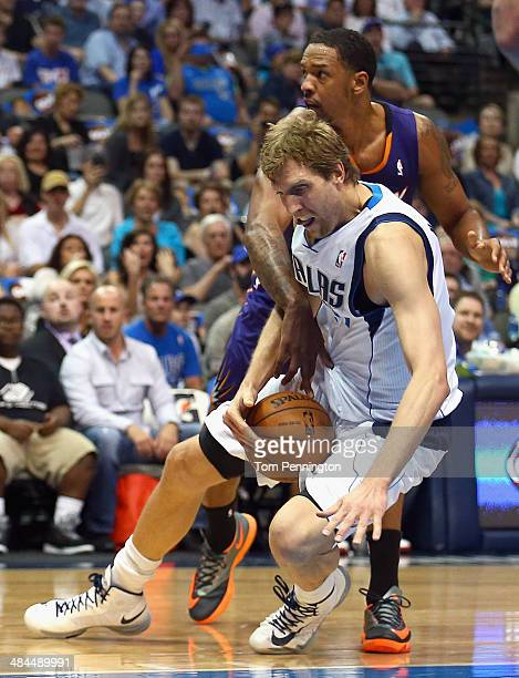 Dirk Nowitzki of the Dallas Mavericks is fouled by Channing Frye of the Phoenix Suns in the first half at American Airlines Center on April 12 2014...
