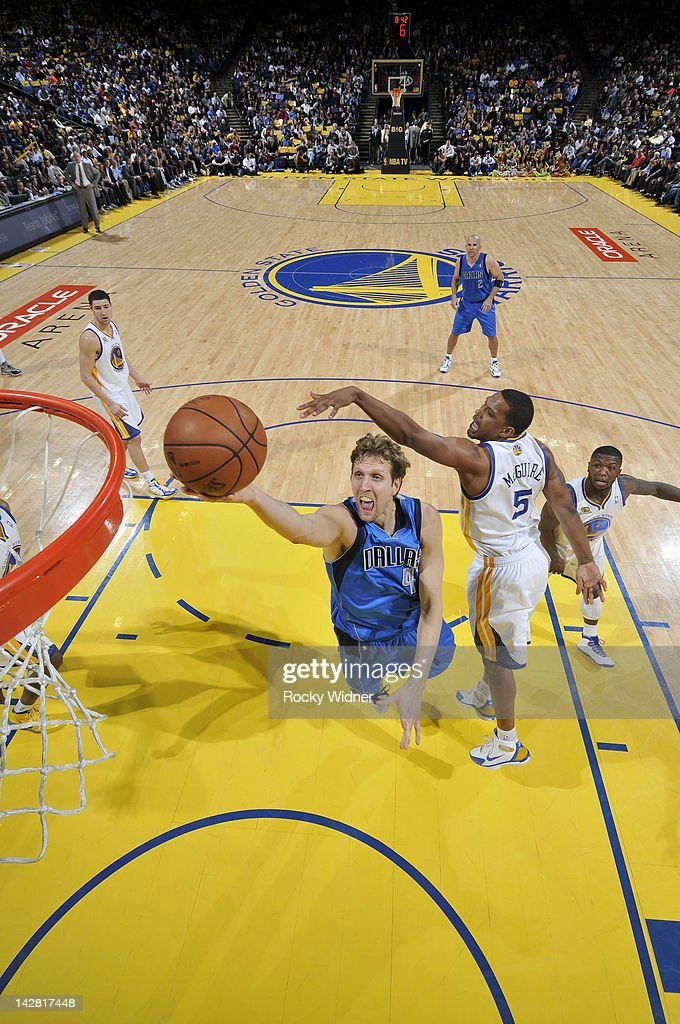 <a gi-track='captionPersonalityLinkClicked' href=/galleries/search?phrase=Dirk+Nowitzki&family=editorial&specificpeople=201490 ng-click='$event.stopPropagation()'>Dirk Nowitzki</a> #41 of the Dallas Mavericks lays the ball up against <a gi-track='captionPersonalityLinkClicked' href=/galleries/search?phrase=Dominic+McGuire&family=editorial&specificpeople=2537986 ng-click='$event.stopPropagation()'>Dominic McGuire</a> #5 of the Golden State Warriors on April 12, 2012 at Oracle Arena in Oakland, California.