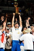 Dirk Nowitzki of the Dallas Mavericks lifts the Larry O'Brien Trophy in celebration after defeating the Miami Heat in Game Six of the 2011 NBA Finals...
