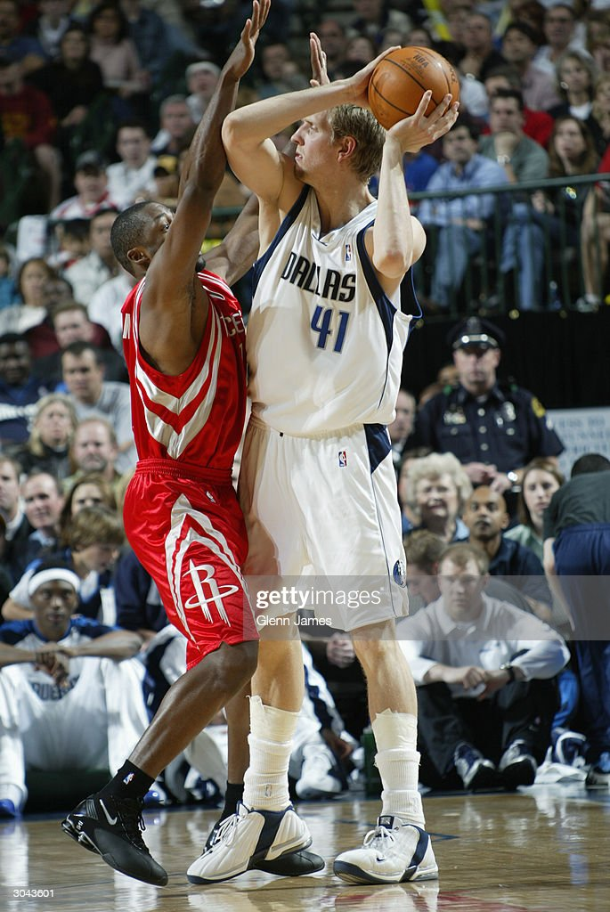 Dirk Nowitzki #41 of the Dallas Mavericks looks to pass over a Houston Rockets defender during the game at the American Airlines Arena on February 21, 2004 in Dallas, Texas. The Mavericks won 97-88.