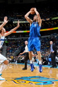 Dirk Nowitzki of the Dallas Mavericks makes a shot passing the 25000 point career milestone against Robin Lopez of the New Orleans Hornets during...