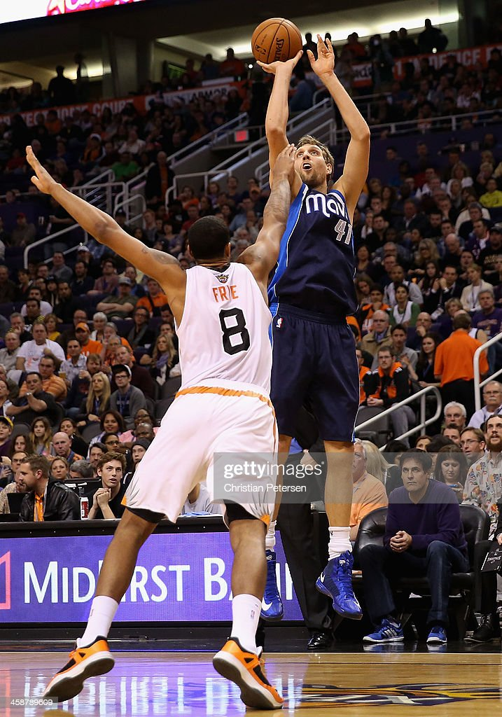 Dirk Nowitzki #41 of the Dallas Mavericks puts up a shot over Channing Frye #8 of the Phoenix Suns during the first half of the NBA game at US Airways Center on December 21, 2013 in Phoenix, Arizona.