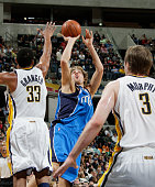 Dirk Nowitzki of the Dallas Mavericks shoots over Danny Granger and Troy Murphy of the Indiana Pacers at Conseco Fieldhouse on November 27 2009 in...