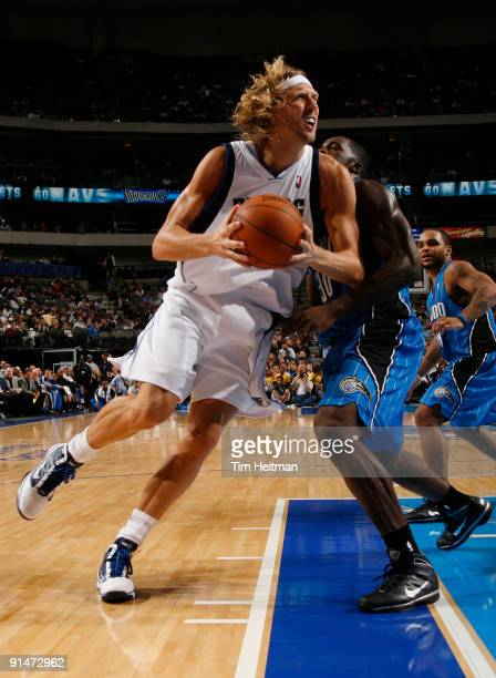Dirk Nowitzki of the Dallas Mavericks spins to the baseline against Brandon Bass of the Orlando Magic in preseason action at the American Airlines...