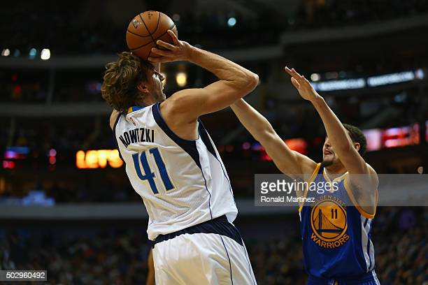 Dirk Nowitzki of the Dallas Mavericks takes a shot against Klay Thompson of the Golden State Warriors at American Airlines Center on December 30 2015...