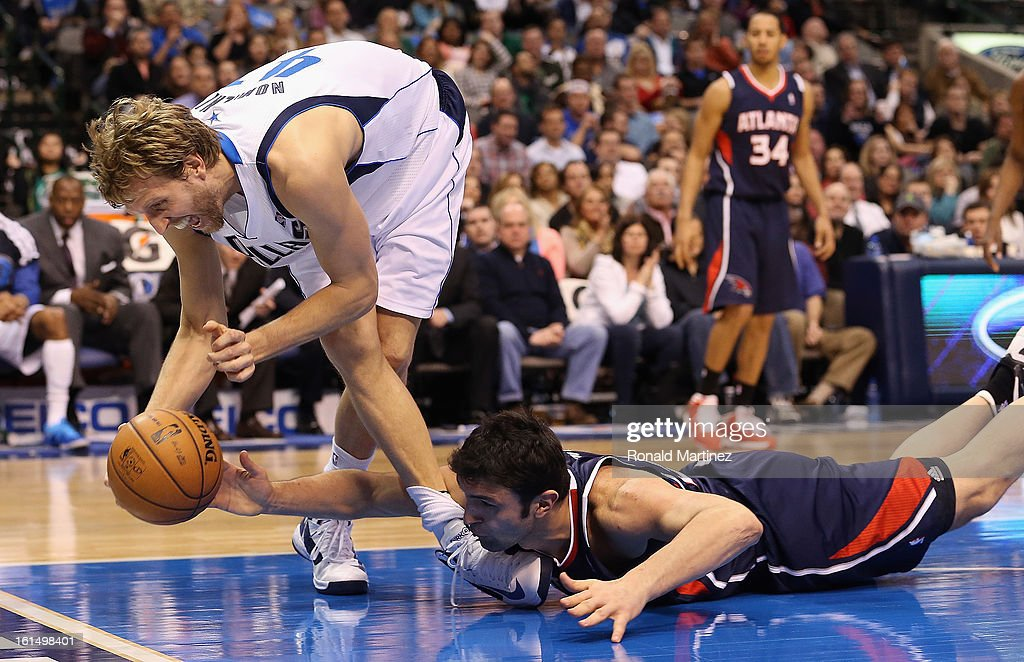 <a gi-track='captionPersonalityLinkClicked' href=/galleries/search?phrase=Dirk+Nowitzki&family=editorial&specificpeople=201490 ng-click='$event.stopPropagation()'>Dirk Nowitzki</a> #41 of the Dallas Mavericks tries to grab a loose ball against <a gi-track='captionPersonalityLinkClicked' href=/galleries/search?phrase=Zaza+Pachulia&family=editorial&specificpeople=202939 ng-click='$event.stopPropagation()'>Zaza Pachulia</a> #27 of the Atlanta Hawks at American Airlines Center on February 11, 2013 in Dallas, Texas.