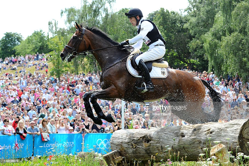 Dirk Schrade of Germany riding King Artus negotiates a log jump in the Eventing Cross Country Equestrian event on Day 3 of the London 2012 Olympic...