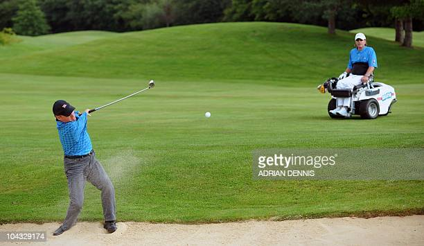 Dirk Ulucle watches Peter Williams play out of a bunker during the second day of the Disabled British Open golf tournament at East Sussex National...